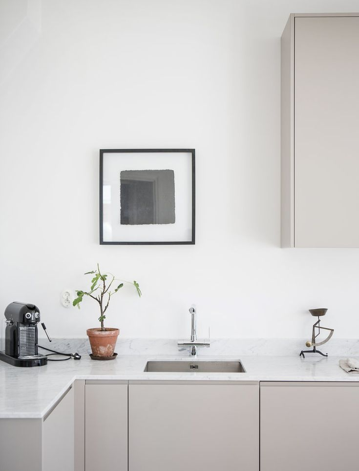 Minimalistic grey kitchen by Nordiska Kök. Clean and elegant kitchen ideal for high ceilings where form and function go hand in hand. The soft greige tones set off the marble worktop. For more kitchen inspiration visit www.nordiskakok.se #kitchen #bespokekitchen #interior #architect #grey #limestone #white #framekitchen #minimalism #minimalistic #wood #kitchendesign #kitchenideas #greykitchen #design #designtrends #beautifulkitchens