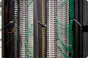 """In this view, you can see the rear, or """"hot"""", side of the server rack at Chicago-1. This is the back of the servers where the power and network connect to the server. This is also where the server exhaust fan is located."""