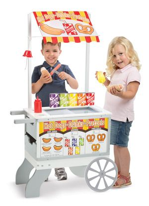 """Snacks & Sweets Food Cart: Savory or sweet? This rolling, reversible snack cart offers a choice of play menus! With the """"Hot Dogs"""" menu and awning on display, kids can reach inside the sliding see-through doors to serve up a hot dog with toppings to order, a soft pretzel with mustard or salt, and more. Flip the awning and menu to """"Ice Cream"""" and reverse the storage drawers, and reach in for cones, scoops, and pull-apart pops for dessert!"""