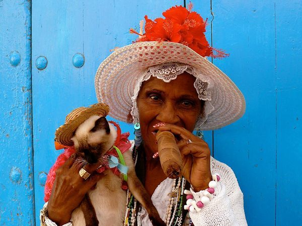 "A colorful Havana woman enjoys an enormous cigar. The smokes are one of Cuba's defining symbols—""Havanas"" are renowned worldwide and have special cache among many aficionados in America, where their import remains illegal."