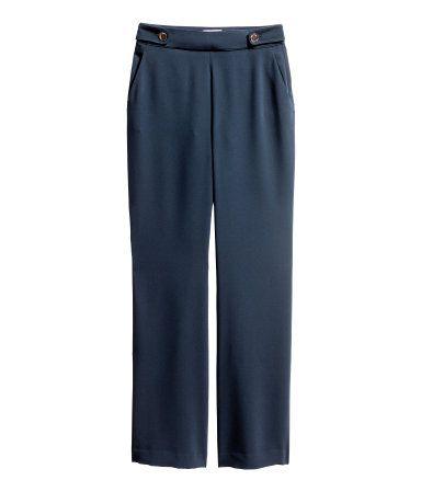 Mörkblå. Ett par kostymbyxor i vävd kvalitet. Byxorna har hög midja och raka, vida ben. Slejf med knapp i sidorna samt dragkedja i ena sidan. Sidfickor.