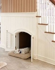 Built-in dog house under the stairs. Dogs have home dreams too! An arched doorway with little french doors makes this dog den look nicer than others I've seen, and more discreet when closed.