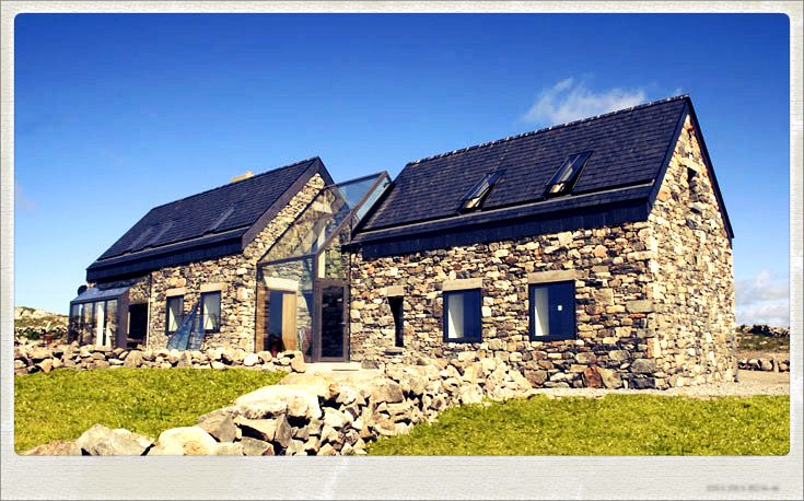 Folan's Cottage in Connemara, Ireland; two crumbling stone cottages were restored and joined by a glassed-in stairwell; designed by Peter Legge Associates