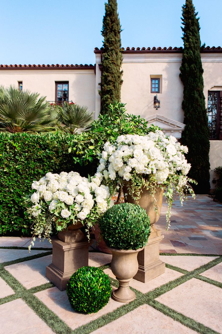 The entrance to the ceremony space was decorated with earth-tone urns filled with arrangements of white roses and hydrangeas, as well as boxwood spheres. #WeddingCeremony Photography: Yvette Roman. Read More: http://www.insideweddings.com/weddings/a-classic-wedding-with-rustic-touches-at-a-villa-in-santa-barbara/674/
