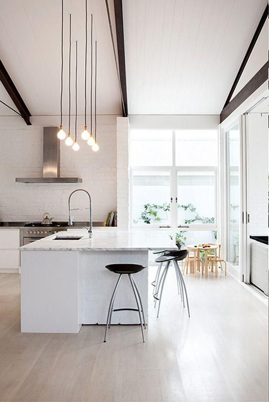 Black and white minimalist, modern, contemporary kitchen with rows of hanging single bulb pendant lights above the carrara marble counter, tall black backless bar stools, exposed black metal beams in the ceiling, a modern stove top hood, high slanted ceilings, tons of natural light and blonde wood dining furniture in the background.