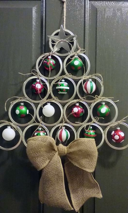"""This mason jar lid Christmas tree door hanger is adorable and so easy to make at home! This was made by Bri Wood and she let me share with you guys! Adorable. Supplies Needed: 15 canning lids 14 small ornament bulbs Clothespins Twine Hot glue gun Metal glue Directions: """"I used the wide mouth canning …"""
