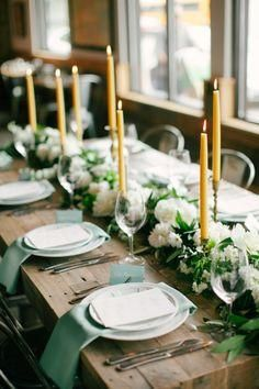 We love this green themed long rustic dinner table -- everything from the gold taper candles and candle sticks to the soft sage green napkins to the low white long centerpieces flower garland and simple wine glasses and flatware setting. Stunning and simple style idea for holiday.
