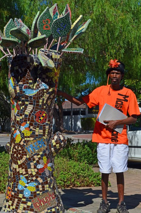 """Mosaic artisan and tour guide Phillip Bicks stands next the """"Tree of Life"""" - artwork he's helped to create throughout Sedgefield."""