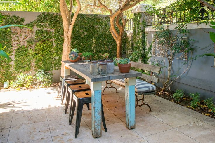 A table set under shady trees in the courtyard garden.