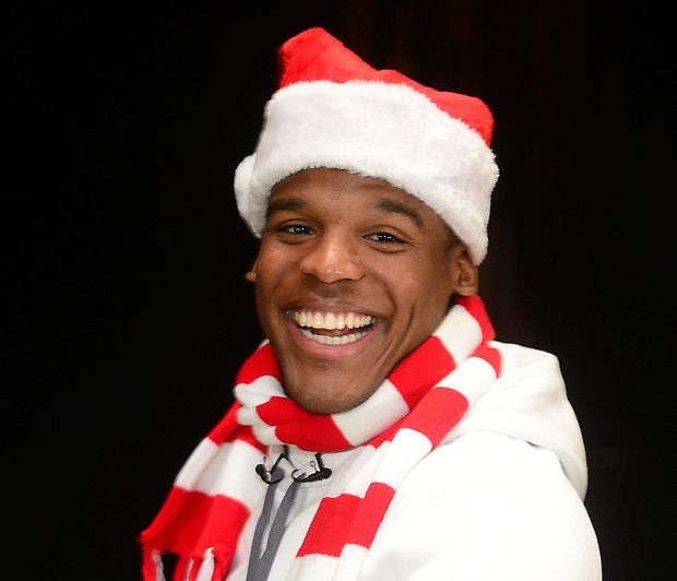 Panthers quarterback Cam Newton laughs as he hands out gift cards to teachers and staff at West Mecklenburg High School Tuesday, Dec. 16, 2014. Newton handed out gift cards and apparel during at four locations across Charlotte as part of his Santa Cam's Surprise Sleigh event.