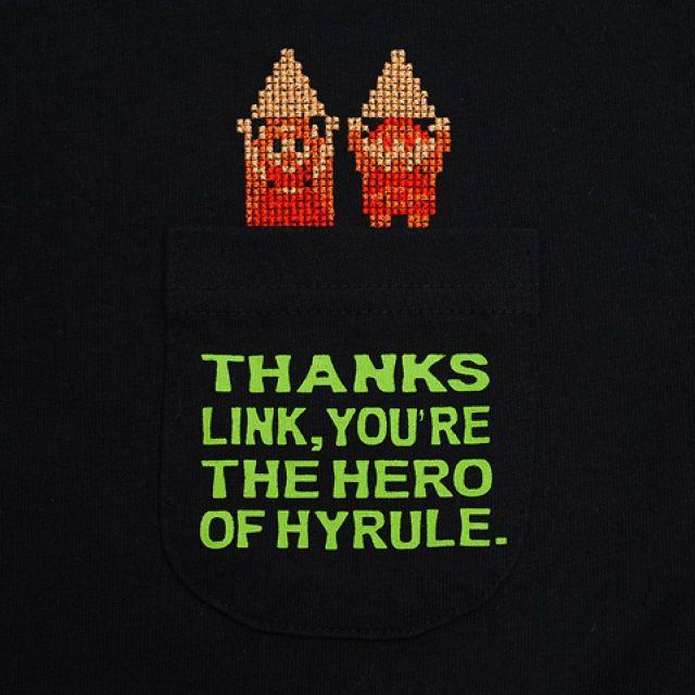 Legend of zelda 1-POINT T  ゲームTシャツをさりげなくさらっと着たい方に向けてキャラクターを一点「クロスステッチ」で刺繍し究極に絞り込んだデザインをプリントしたシンプルイズベストなワンポイントデザインをポケット付きTシャツ、フットボールTシャツに落とし込んだKOGの新しいシリーズです。  ゼルダの伝説のエンディングシーンでゼルダ姫とリンクがトライフォースを掲げる姿をクロスステッチで仕上げました。ポケットの文字はエン ディングでの台詞を、バックプリントにはあの有名な台詞「ミンナニハナイショダヨ」の英文を配置しました。