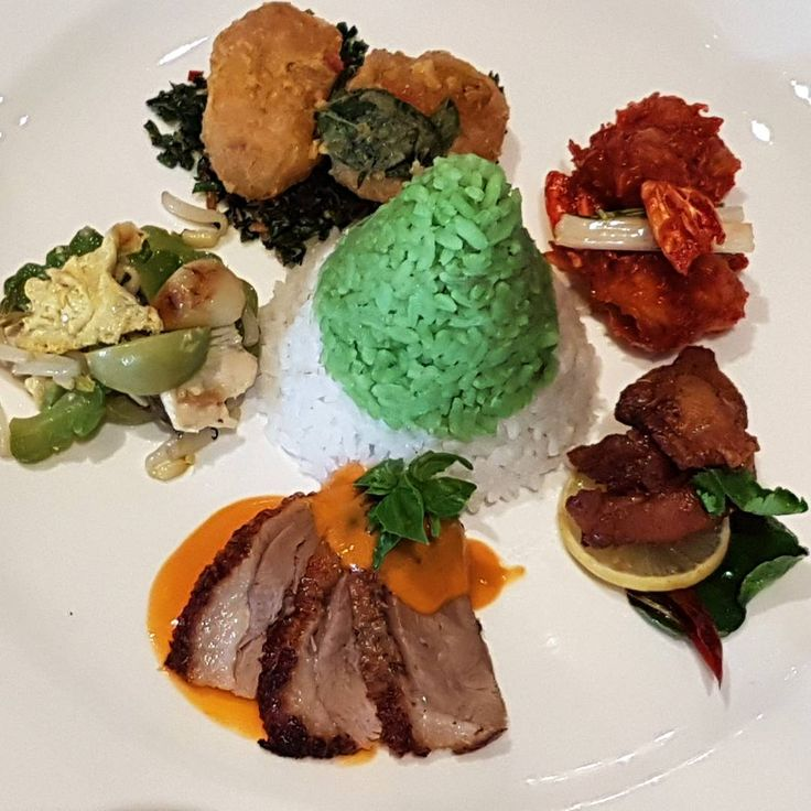 Classic Indonesian Rice dish with Mini Tumpeng with duck curry, prawn chillies balado, ayam tangkap - fried-chicken with herbs, spices, mixed leaves - curry, pandanus  and lime leaves, tofu and salted eggs and stir-fried bitter gourd.  Tumpeng is a cone of rice served with many different types of protein and normally served at celebrations on Java. Nasi Kuning or yellow rice is used for Tumpeng, normally, cooked with turmeric, lemon grass, pandanus leaves, coconut milk and lime leaves. The…