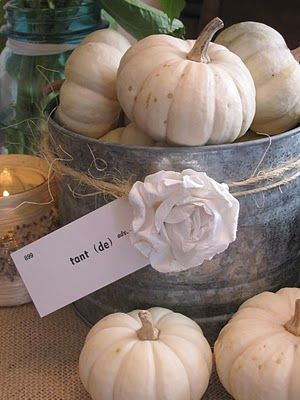 Use a basket or tub decorated with rose and raffia like this to display small pumpkins.  Love this.