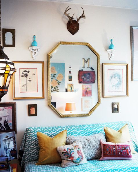 Bohemian Living Room - A gold mirror hung above a bench covered with patterned blue fabric via Lonny