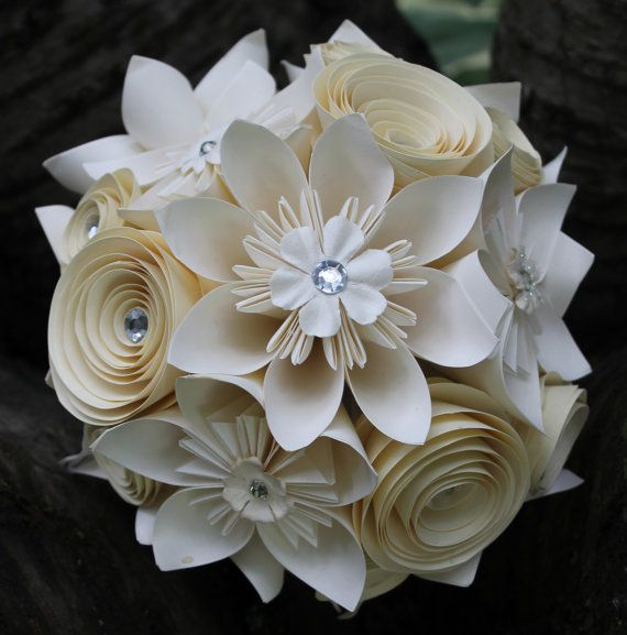 This elegant and unique bouquet is made out of nine origami flowers in two sizes, nine spiral flowers in two sizes and one large origami