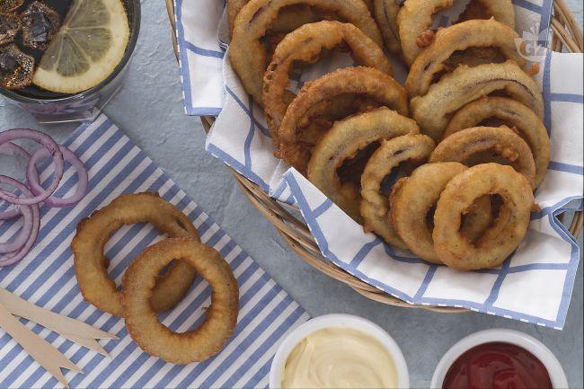 Gli anelli di cipolla in pastella vengono preparati immergendo gli anelli di cipolla in una pastella piuttosto densa e poi fritti in olio di semi bollente: sono ottimi sia caldi che freddi.
