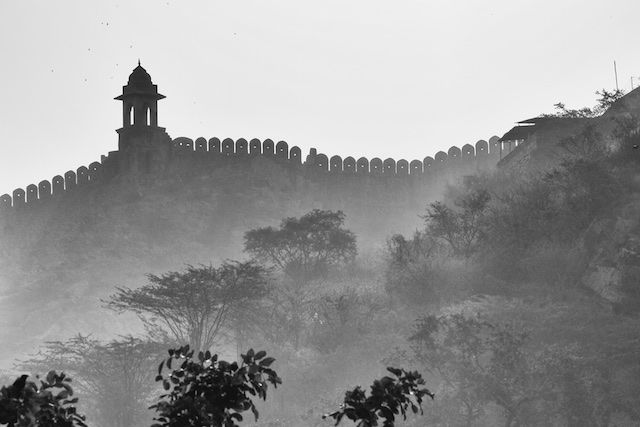 Mist flows through the trees surrounding the massive fort walls in Jaipur.