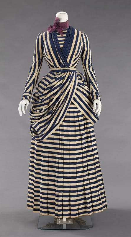 Smart Day dress for activities (1885-1888). Navy & cream striped. Pleated skirt ~ shortened for walking ~ with requisite bustle behind. Fitted bodice with a wrapped-style peplum, which sweeps back into the bustle. Belted, cinched waist. Plum silk ribbon choker worn at the throat for accent.