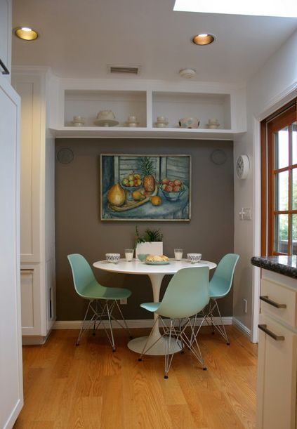 This area is organized near an accent wall and features a white, round table and three pale turquoise Eames side chairs. On the wall there's also a painting with a similar color palette.