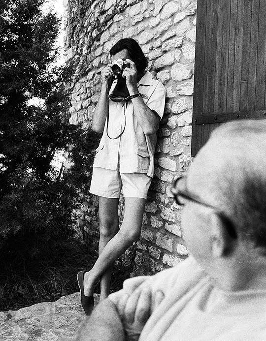 La silueta larguísima, la cara escondida detrás de una espesa barba negra y de unas enormes gafas, la ropa y el calzado modestísimos. Julio Cortázar, cámara en mano.