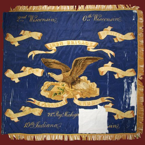 The Iron Brigade Civil War Flag of the 2nd, 6th and 7th Wisconsin, the 19th Indiana and the 24th Michigan. This flag was commissioned by citizens of Wisconsin, Indiana and Michigan for presentation to the Iron Brigade in 1863. Manufactured by Tiffany and Co., New York City, the flag is made of high quality blue silk, with deep gold fringe and intricate brocade embroidery. The flag was not regulation and therefore not permitted in the field, so it was sent to Madison, Wisconsin for…