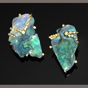 Lightning Ridge Opals: Of asymmetrical design, this pair of earrings incorporates a thick seam of black opal cut into two sections, weighing approximately 58.07 carats, having a vivid green play-of-color, contour polished to reveal its vibrant gem-quality which graduates at one end to a white crystal opal. The 18K yellow gold mount is enhanced with 0.60 carats of brilliant-cut yellow diamonds; no designer attribution