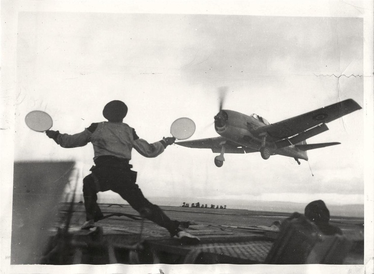 "1944- Signalman gives the all clear as Grumman ""Hellcat"" comes in for a landing aboard the H.M.S. RAVAGER."