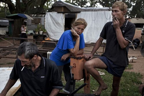 A family smokes together at a squatter camp
