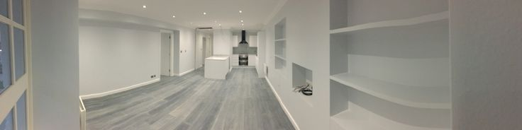 Grey wooden floors, white features, light blue walls, bespoke joinery, open plan living room and kitchen.