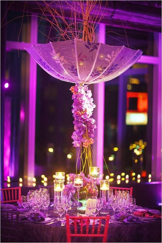Continuing the umbrella theme throughout the wedding adds continuity. This artistic style looks amazing combined with tall flowers and purple lighting.