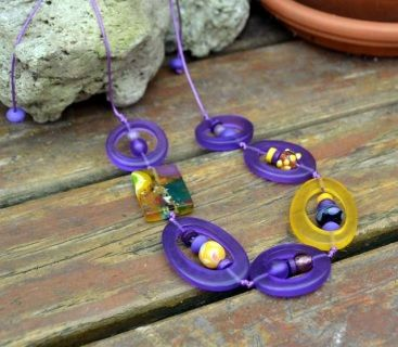 """This adjustable necklace is made up of six doughnut shaped beads in purple and yellow transparent resin and one rectangle multi coloured resin bead.   Threaded into each bead is glass, resin and wooden beads and all are threaded and double knotted onto 1mm waxed purple cotton cord.   The necklace is finished with wood and two resin beads with which you can adjust the length of the necklace from fashionably long to any length you require.   Toni says: """"Purple and yellow is a fabulous colour…"""