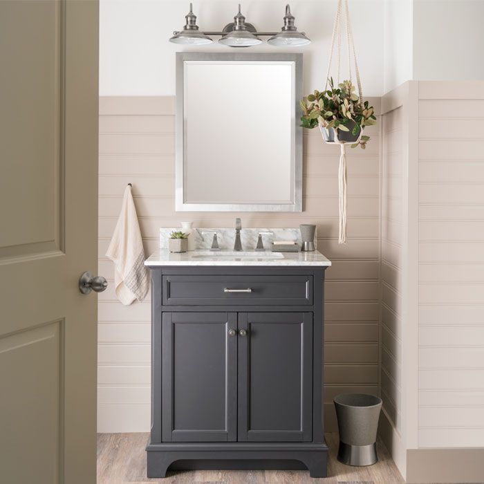 Start your small bathroom updates right away. Anchor the new look with a gray allen + roth™ vanity and carrara marble countertop. Then focus on fine metallic finishes by adding a stainless widespread faucet, brushed-nickel mirror, antique pewter vanity light and a brushed-nickel towel ring. Shiplap-style wall panels and wood-look vinyl plank flooring add a rustic yet refined vibe. The wall panels are painted light brown, while the rest of the walls are white.