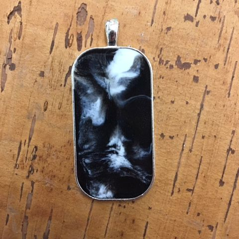 I can see a face in this resin pendant, can you ?