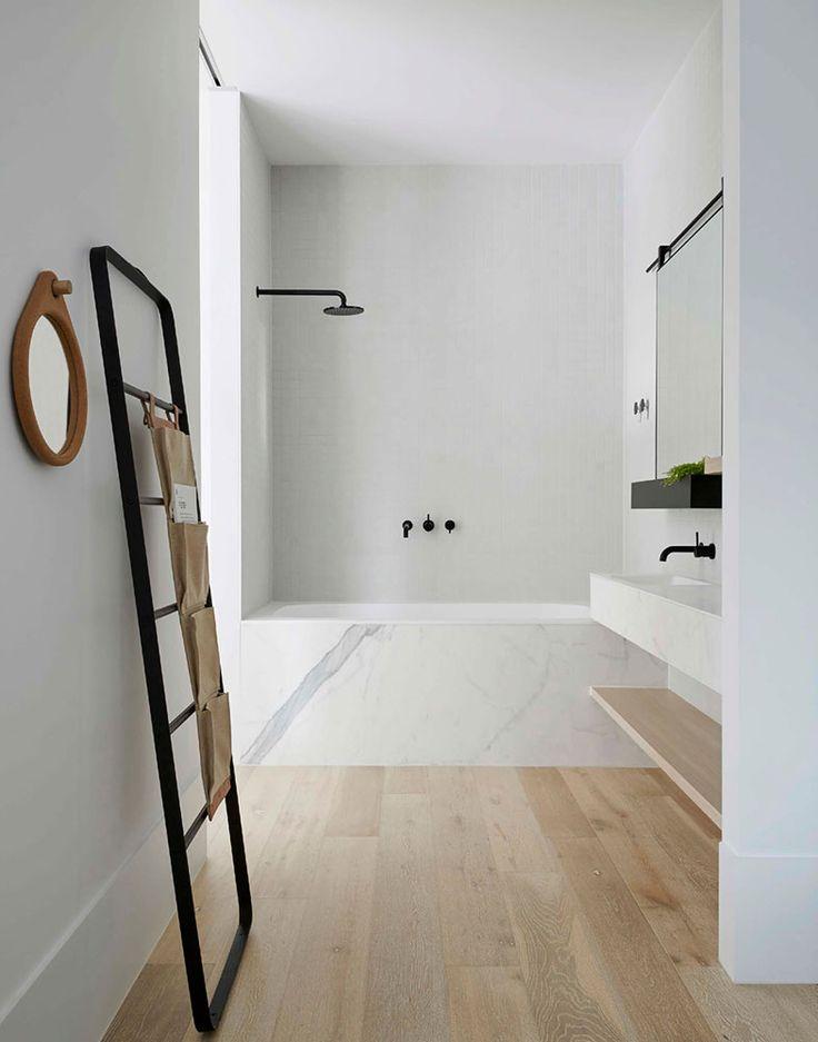 Simply elegant bath; marble tub surround, white wash oak floor; black wall mounted faucets