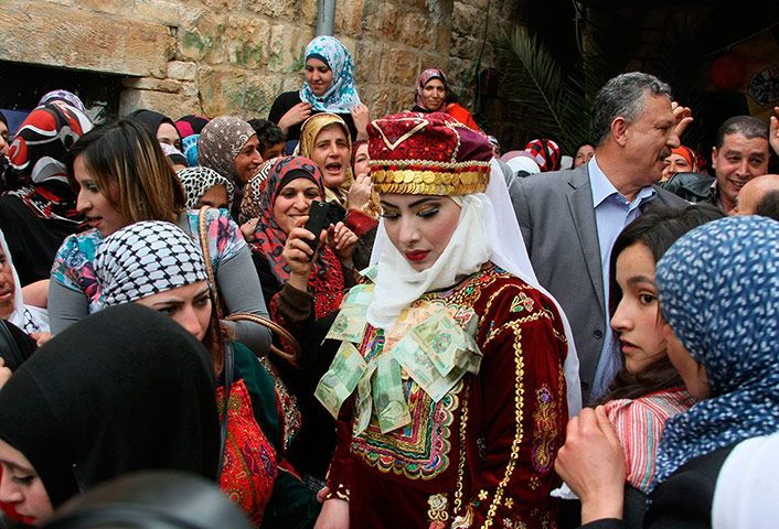 Deir Estia, Palestine: Palestinian bride Mhaha Salam is pinned with paper money which is traditionally given as wedding gifts. Photograph by Jaafar Ashtiyeh/AFP/Getty Images