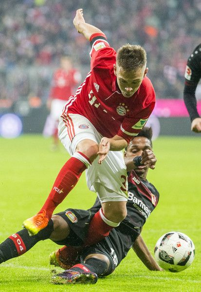 Joshua Kimmich (L) of FC Bayern Muenchen is challenged by Wendell of Bayer 04 Leverkusen during the Bundesliga match between Bayern Muenchen and Bayer 04 Leverkusen at Allianz Arena on November 26, 2016 in Munich, Germany.