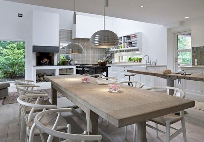 Beautiful modern open-plan kitchen /dining space with white wishbone chairs paired with a natural oak table