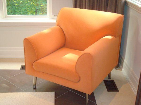Custom made orange armchair with metal legs.