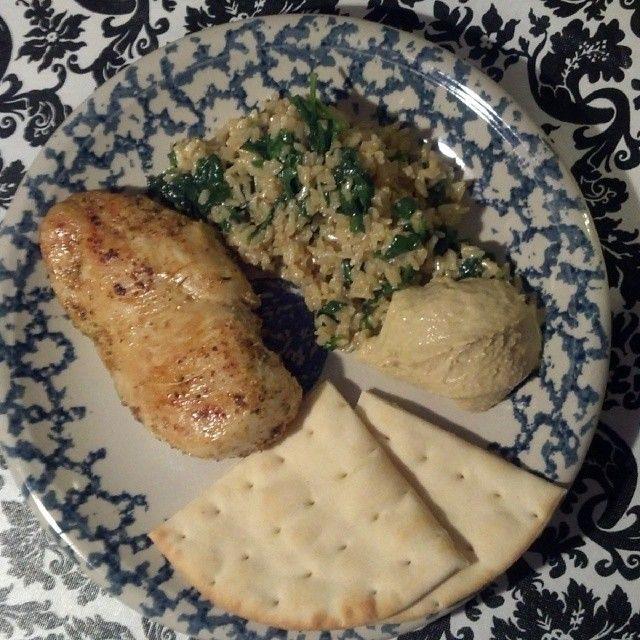 Grilled chicken, spinach rice, pita bread and hummus.
