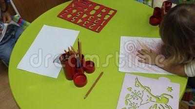 Preschoolers to kindergarten during educational activities - little girl drawing with crayons.