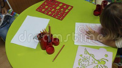Preschoolers to kindergarten during educational activities - little girl drawing with crayons.