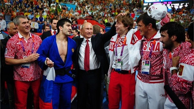 Russian President Vladimir Putin celebrates Tagir Khaibulaev of Russia's gold medal in the Men's -100 kg Judo on Day 6 of the London 2012 Olympic Games at ExCeL