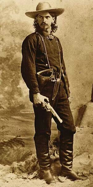 """Wild"" Ben Raymond, with .44 Merwin & Hulbert in one hand and a Smith & Wesson No. 3 New model in his holster. He wears a Bowie knife around his neck. He worked as a mine guard, posed for his photograph in Leadville, Colorado, in 1879, holding a First Model open top Merwin Hulbert Frontier Army revolver. Although the arm is believed to have been a photographer's prop, it nonetheless shows the Merwin's presence in the Wild West."
