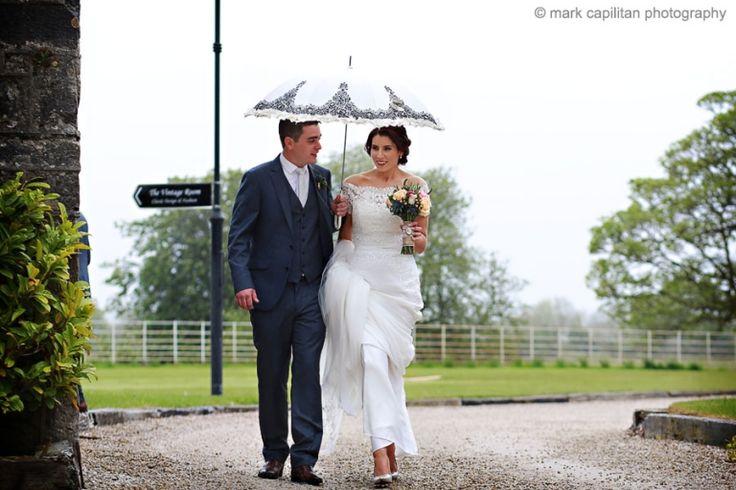 Bride & groom walking in the rain under an umbrella Castle Dargan Ireland wedding photographer Sligo
