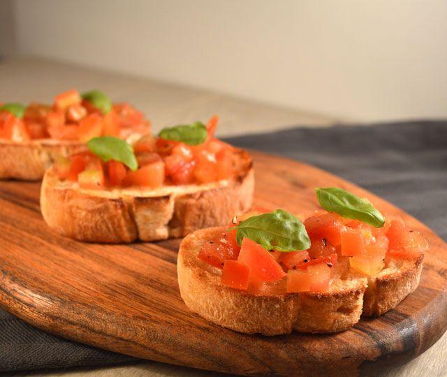Bruschetta, een Italiaanse klassieker! Gegrild brood, ingesmeerd met knoflook en een paar druppels olijfolie. Recept: Bruschetta met Tomaat & Basilicum.