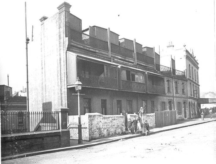 Looking S towards SE corner of Cumberland Street and Argyle Street.	 Unusual set of 2-storeyed terraces (71-79 Cumberland Street), below road level, having a wrought iron parapet behind which on the roof are three weatherboard sheds. The enclosed verandahs have wrought iron balconies. A decorative cast iron gaslamp stands at the entrance to Playfair Stairs (down to Gloucester Street). At L is the fence above Argyle Street. c1909-13 NSCA CRS 51, Demolition books, 1900-1949