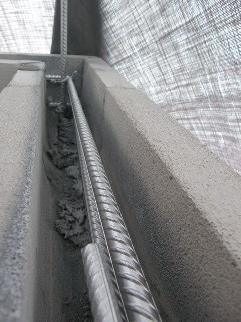 Autoclaved aerated concrete insulating the steel reinforced bond beam.  Topping each story, it ties to the vertical.