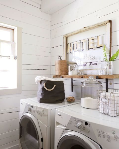 A vintage hotel sign, along with glass canisters for detergent and such, prettifies the laundry room. The walls are painted Simply White by Benjamin Moore.