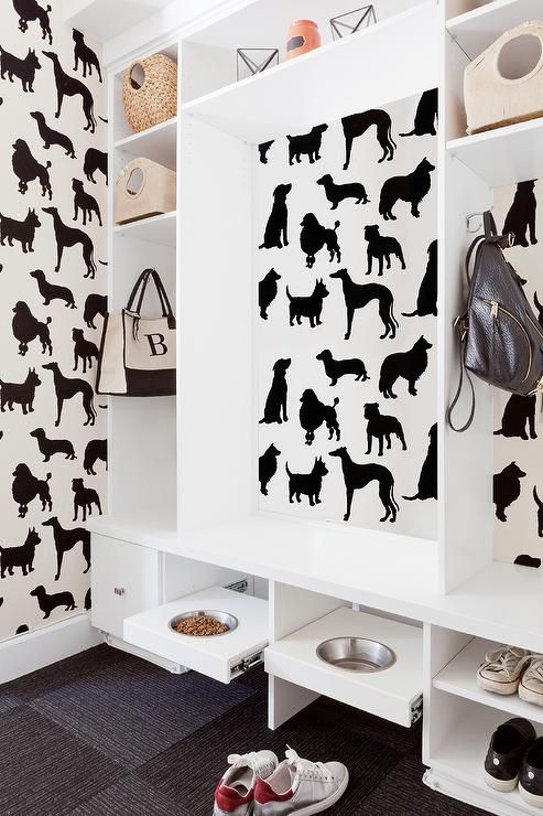 Spectacular mudroom and pt room combo features walls clad in black and white dog wallpaper, Osborne & Little Best In Show Wallpaper, lined with a built in bench flanked by open shelving placed over built-in pull out dog food bowls.