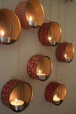 tealight candles in tuna cans suspended on walls.